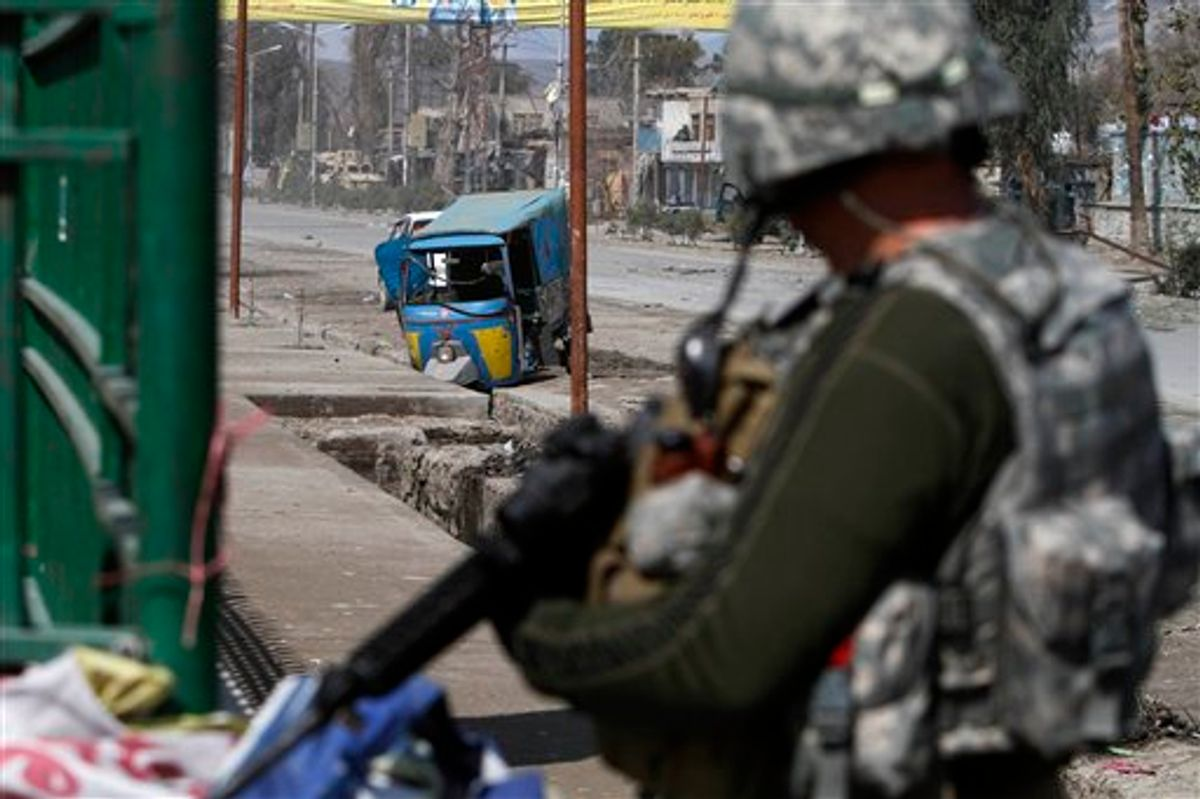 US solider stands guard near the site of explosion in Jalalabad, Afghanistan, Monday, March, 7, 2011. An Afghan Interior Ministry spokesman says a roadside bomb in the eastern city of Jalalabad has killed two policemen and wounded another 25 people.(AP Photo/Rahmat Gul) (AP)
