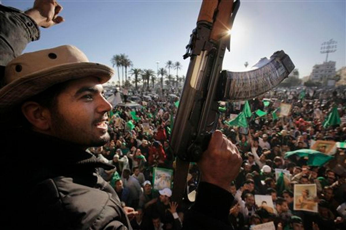 Pro-Gadhafi soldiers and supporters gather to celebrate in Green Square, Tripoli, Libya Sunday, March 6, 2011. Thousands of Moammar Gadhafi's supporters poured into the streets of Tripoli on Sunday morning, waving flags and firing their guns in the air in the Libyan leader's main stronghold, claiming overnight military successes. (AP Photo/Ben Curtis) (AP)