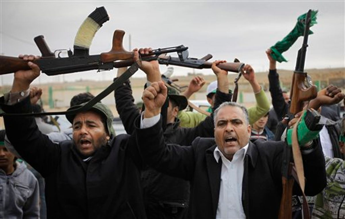 Pro-Gadhafi fighters raise their weapons as they are pictured during a government-organized visit for foreign media in Bin Jawwad, 350 miles (560 kilometers) southeast of the capital Tripoli, in Libya Saturday, March 12, 2011. The world moved a step closer to a decision on imposing a no-fly zone over Libya but Moammar Gadhafi was swiftly advancing Saturday on the poorly equipped and loosely organized rebels who have seized much of the country. (AP Photo/Ben Curtis) (AP)