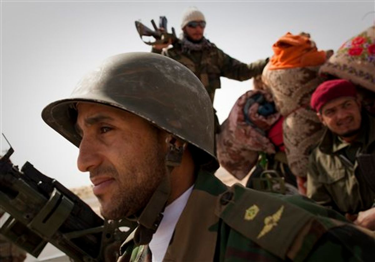 Libyan rebels stop at a checkpoint in Al-Egila, east of Ras Lanuf, eastern Libya, Sunday, March 27, 2011. The rebels claim that they have entered Ras Lanuf.  The rebels claim that they have entered Ras Lanuf. Libyan rebels took back a key oil town and pushed westward Sunday toward the capital, seizing momentum from the international airstrikes that tipped the balance away from Moammar Gadhafi's military.  Brega, a main oil export terminal in eastern Libya, fell after a skirmish late Saturday and rebel forces moved swiftly west, seizing the tiny desert town of Al-Egila  a collection of houses and a gas station on their way to the massive oil refining complex of Ras Lanouf. (AP Photo/Anja Niedringhaus) (AP)