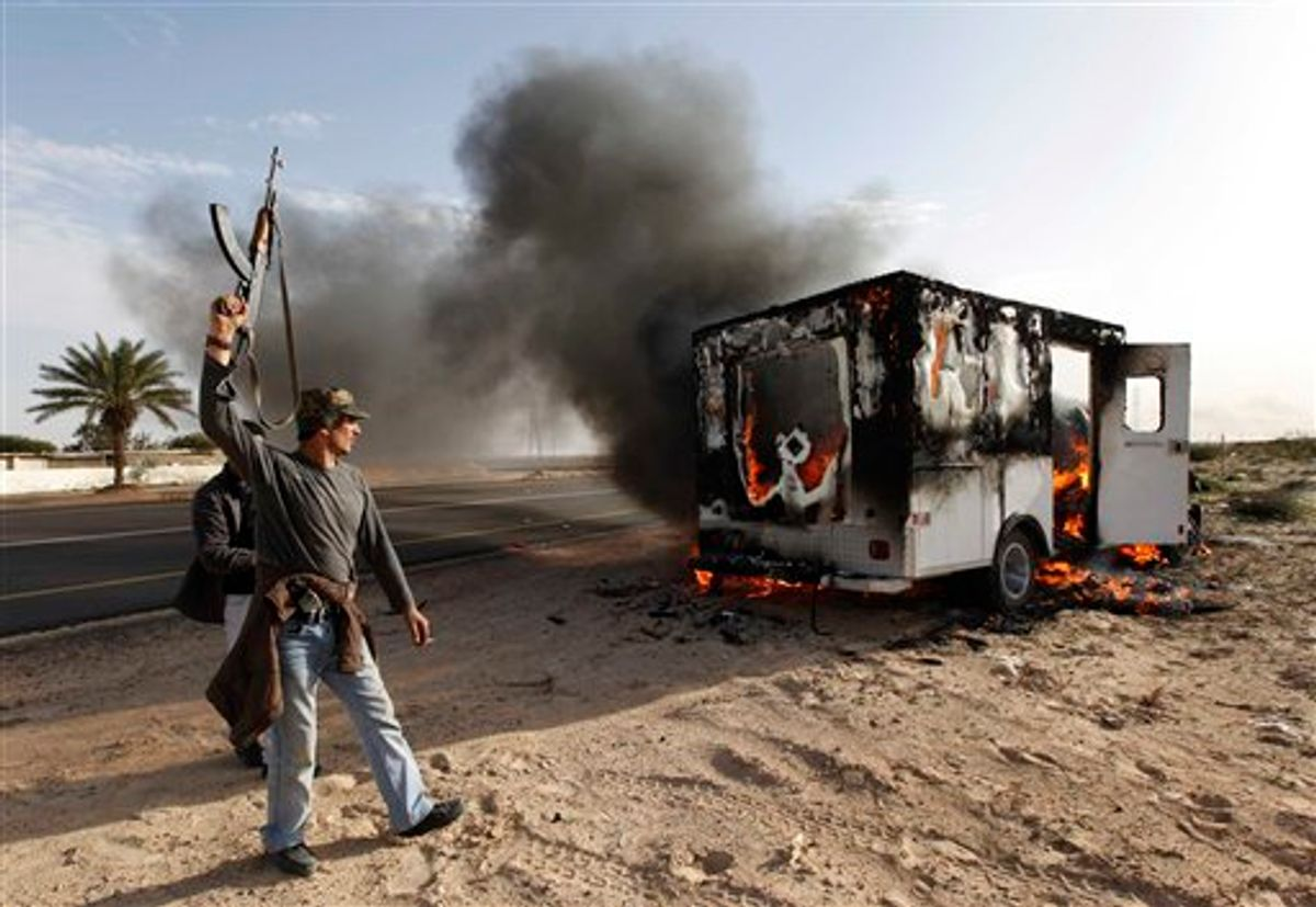 A Libyan rebel celebrates next to a burn pro-Moaamar Gadhafi fighters vehicle in the town of Brega, east of Libya, oWednesday March 2, 2011. Regime opponents battled forces loyal to Libyan leader Moammar Gadhafi who tried Wednesday to retake a key oil installation in a counteroffensive Wednesday against the rebel-held eastern half of the country. At one point in the flip-flopping battle, anti-Gadhafi fighters cornered the attackers in a nearby seaside university campus in fierce fighting that killed at least five. (AP Photo/Hussein Malla) (AP)