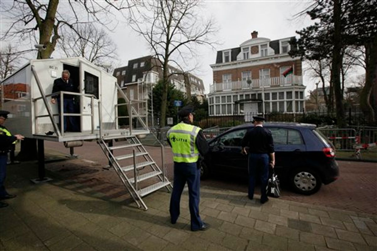 Dutch police change guard duty as a pre-Gadhafi flag, chosen by forces fighting against Moammar Gadhafi, outside right window on first floor, flies outside the Libyan consulate in The Hague, Netherlands, Wednesday March 9, 2011. The International Criminal Court, based in The Hague, recently presented an overview of the alleged crimes committed in Libya since Feb. 15 2011. (AP Photo/Peter Dejong) (AP)