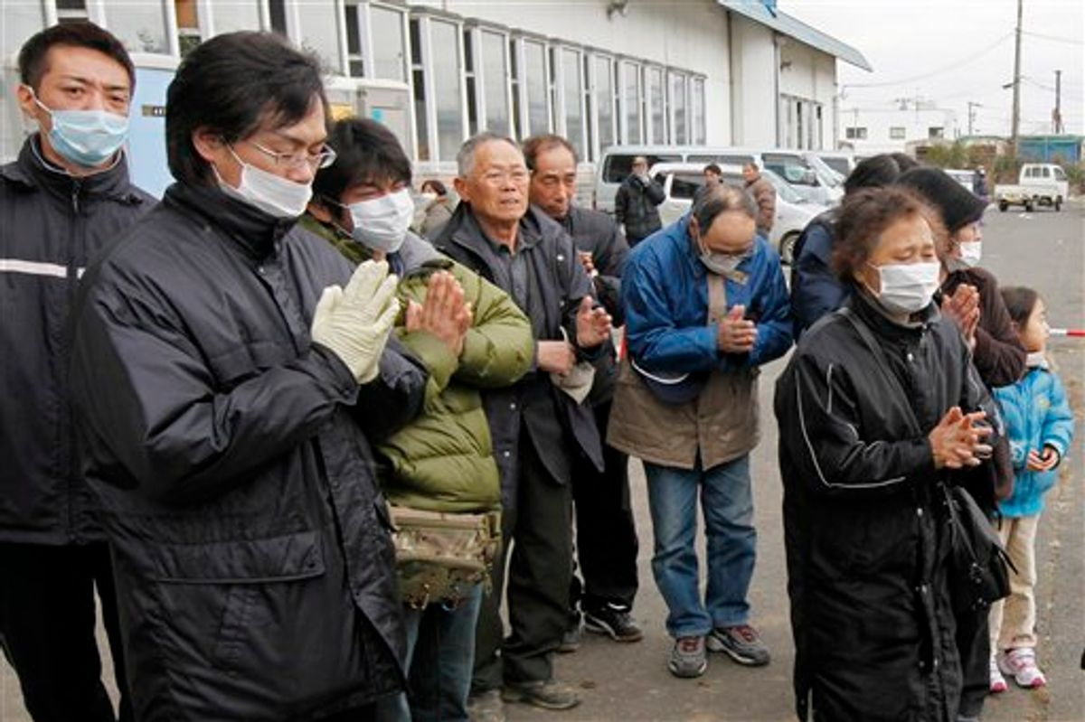 Residents pay their last respects to a victim as a van carrying the coffin leaves a temporary morgue at a bowling alley in Natori, Miyagi Prefecture Monday, March 21, 2011 as the death toll continues to rise following the March 11 earthquake and tsunami that devastated the northeast coast of Japan.  (AP Photo/Mark Baker)  (AP)