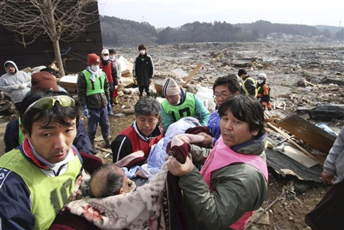 CORRECTS PREFECTURE (STATE) - Rescue workers carry an elderly man found alive by tsunami survivors buried under rubble along a slope of a hill in Minamisanrikucho in Miyagi Prefecture (state) Monday, March 14, 2011, three days after a powerful earthquake-triggered tsunami hit the country's northeast coast. (AP Photo/The Yomiuri Shimbun, Hiroaki Ohno) JAPAN OUT, CREDIT MANDATORY (AP)