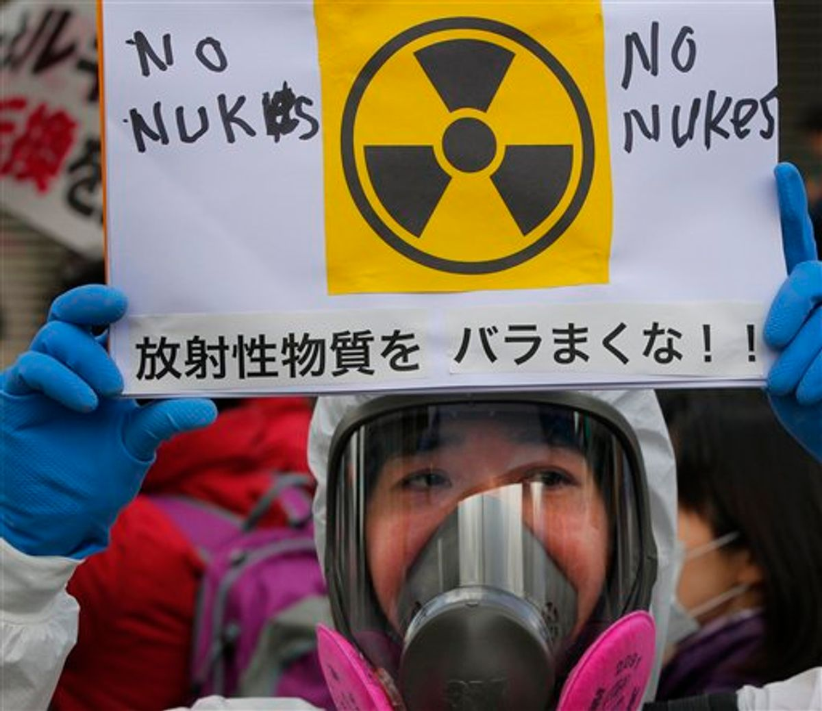 """A protester in protective mask holds a placard during an anti nuclear rally in Tokyo, Sunday, March 27, 2011. Leaked water in Unit 2 of the Fukushima Dai-ichi plant measured 10 million times higher than usual radioactivity levels when the reactor is operating normally, Tokyo Electric Power Co. spokesman Takashi Kurita told reporters in Tokyo. The placard has a message that reads """"Don't spread radioactive substance."""" (AP Photo/Itsuo Inouye) (AP)"""
