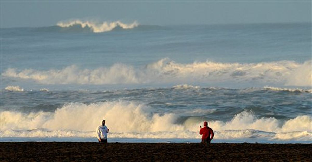 With a tsunami warning in effect for Northern California, two men watch the waves at San Francisco's Ocean Beach on Friday, March 11, 2011. The tsunami warnings came after a 8.9-magnitude earthquake struck Japan. (AP Photo/Noah Berger) (AP)