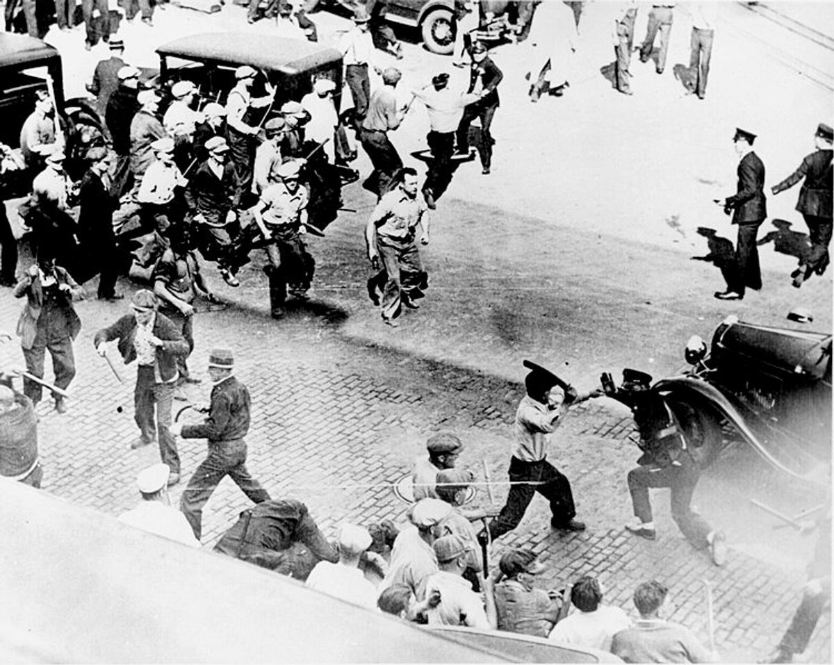 Striking teamsters armed with pipes clash with police in the streets of Minneapolis, June 1934.
