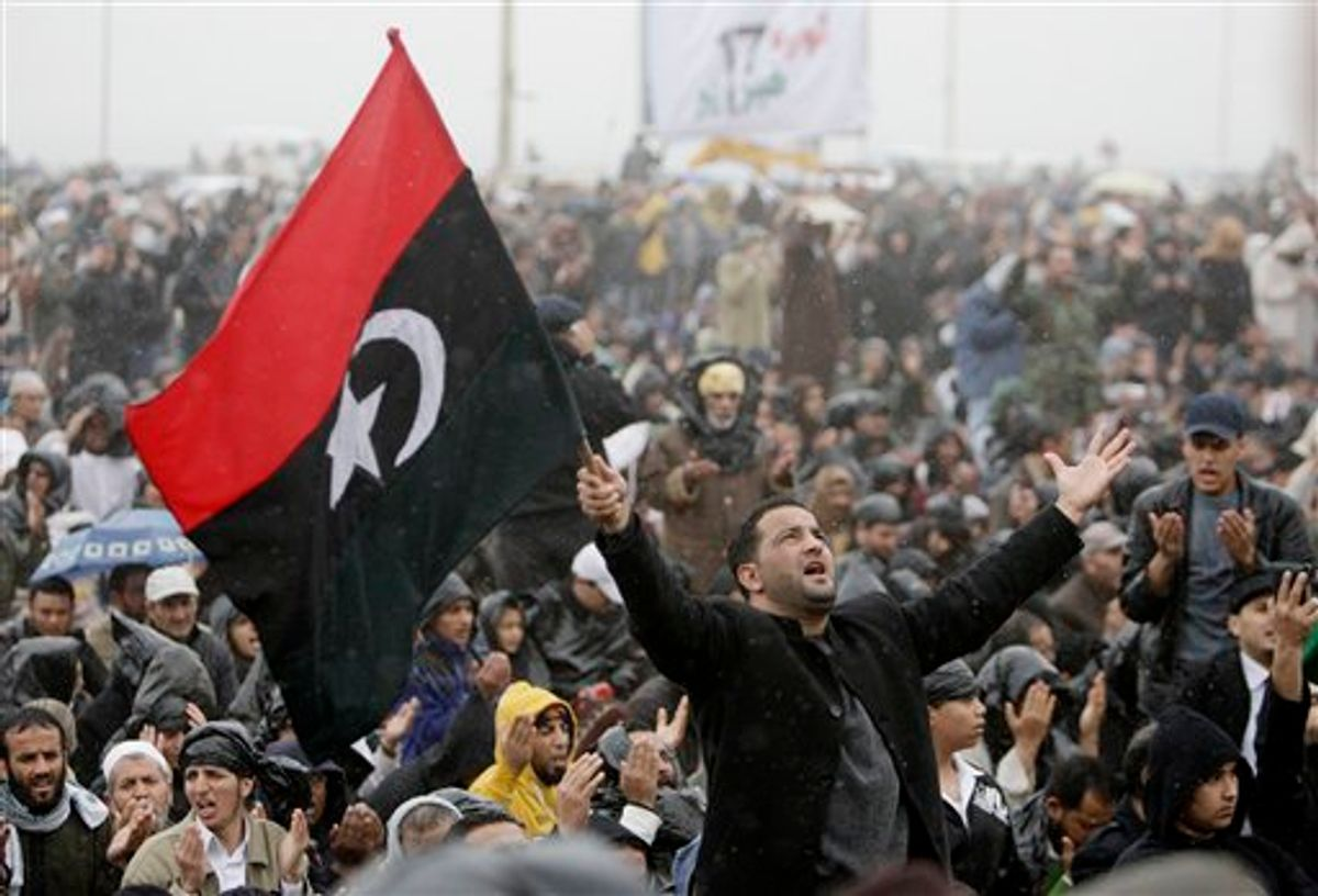 An anti-Libyan Leader Moammar Gadhafi protester prays as he holds the old Libyan flag, during the Friday prayer at the court square, in Benghazi, eastern Libya, Friday March 4, 2011. Fighters loyal to Moammar Gadhafi set up checkpoints in Tripoli, searching cars, ahead of planned anti-government protests Friday, raising fears of new bloodshed in the Libyan capital where a heavy crackdown the past week has spread fear among residents. (AP Photo/Hussein Malla) (AP)