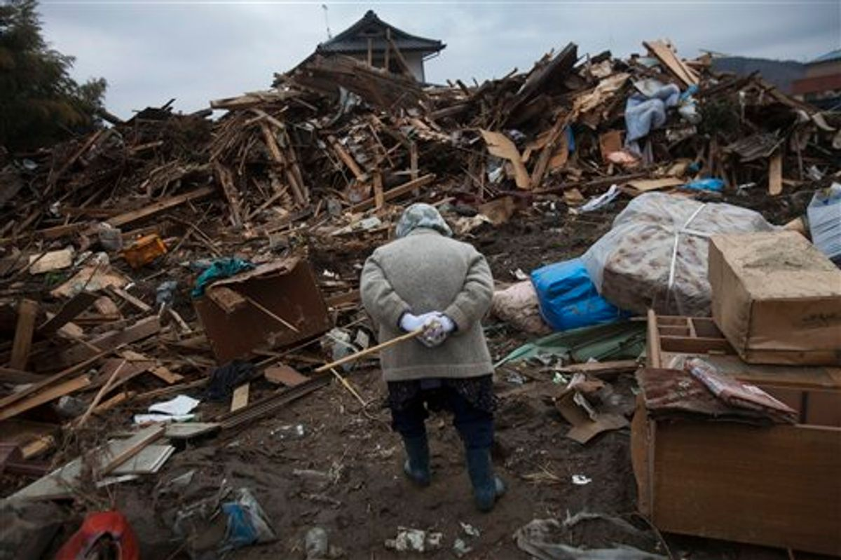 An elderly Japanese woman searches for her belongings in the March 11 earthquake and tsunami-destroyed town of Rikuzentakata, northeastern Japan, Monday, March 21, 2011. (AP Photo/David Guttenfelder) (AP)