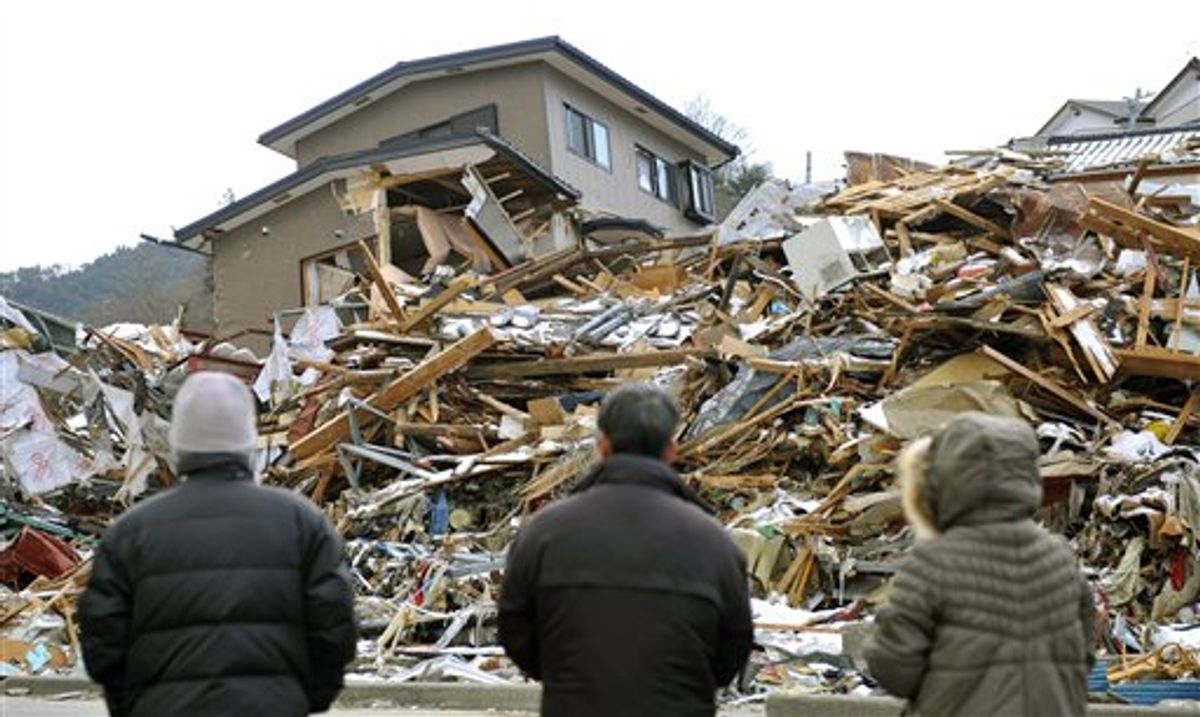 Family members stand in front of their collapsed house in Onagawa, northern Japan Friday, March 18, 2011, one week after a massive earthquake and tsunami.  (AP Photo/Kyodo News) JAPAN OUT, MANDATORY CREDIT, NO LICENSING IN CHINA, HONG KONG, JAPAN, SOUTH KOREA AND FRANCE (AP)
