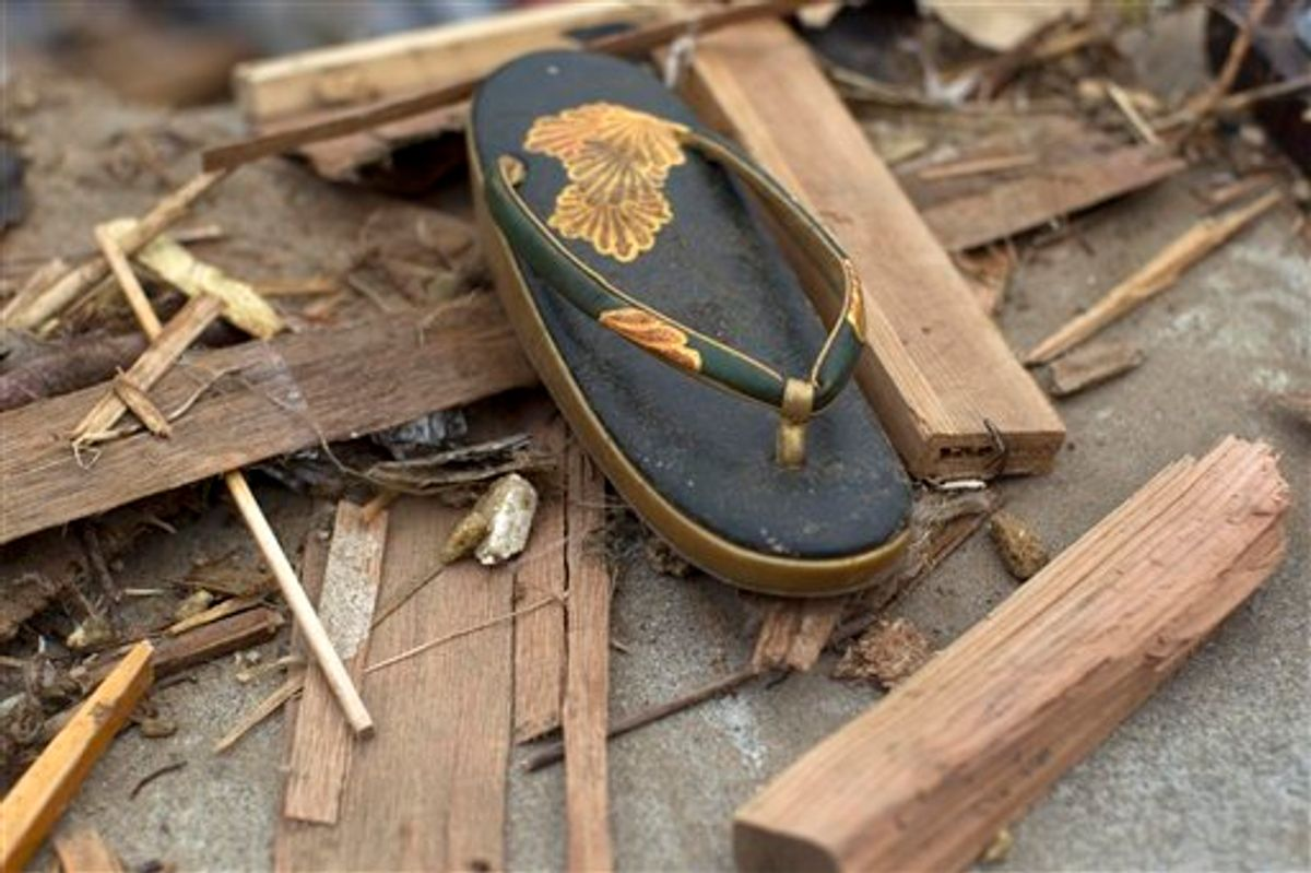 A traditional Japanese sandal, worn with formal kimono dress, lies in the rubble in the earthquake and tsunami destroyed town of Onagawa, Miyagi Prefecture, northeastern Japan Sunday, March 20, 2011. (AP Photo/David Guttenfelder) (AP)