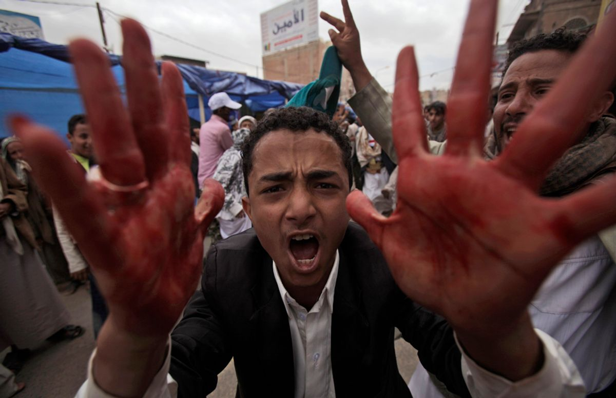 An anti-government protestor shouts with blood on his hands during clashes in Sanaa, Yemen, Friday, March 18, 2011.