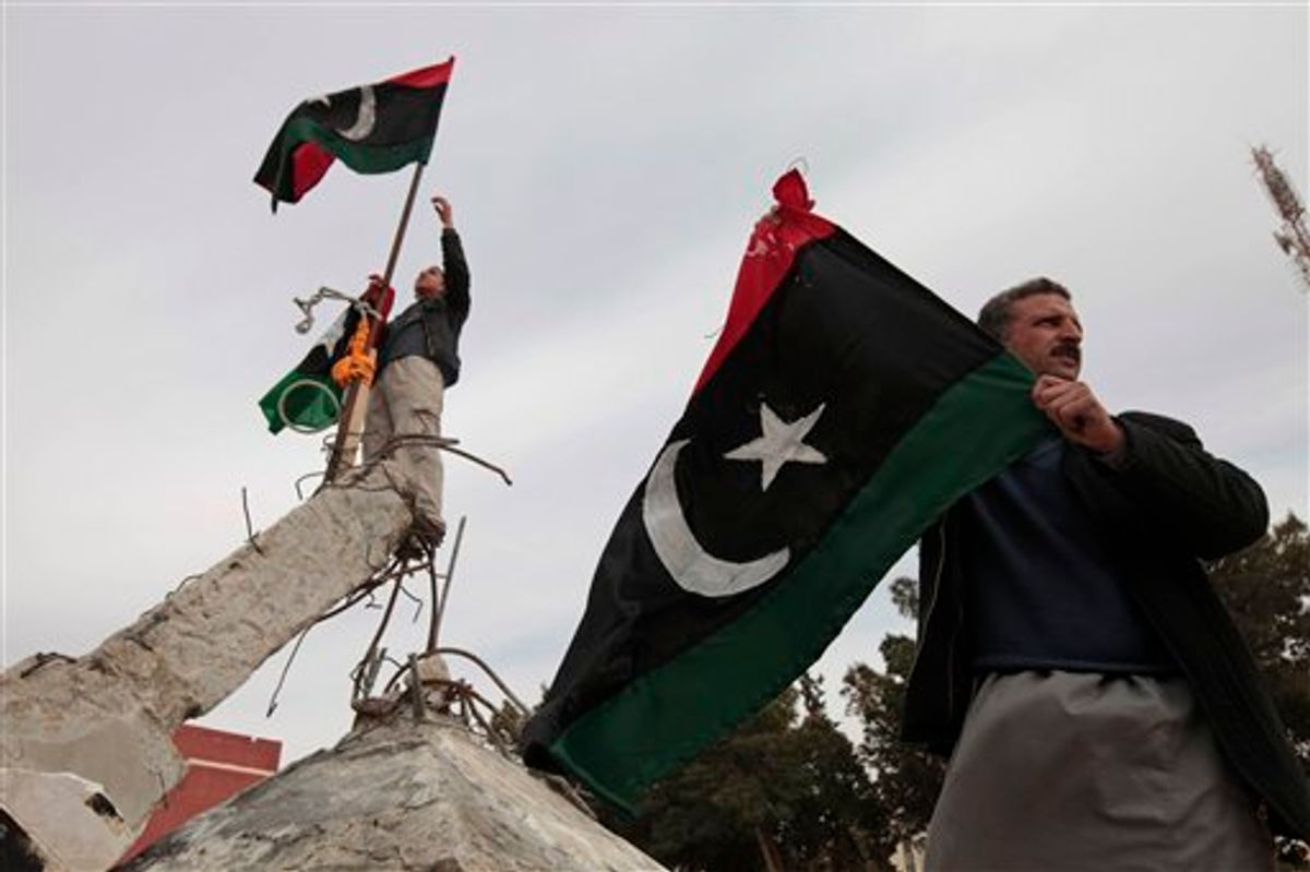 Libyans wave Libyan monarchist-era flags on a monument in the southwestern town of Nalut, Libya,  Monday, Feb. 28, 2011. The town is currently in control of the Libyan anti-government forces. (AP Photo/Lefteris Pitarakis) (AP)