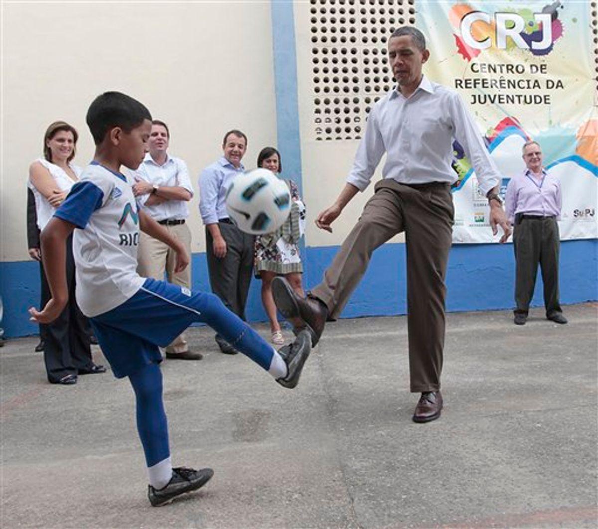 U.S. President Barack Obama practices his soccer dribbling abilities as he plays with local children during his tour of the Ciudad de Deus Favela in Rio de Janeiro, Brazil, Sunday, March 20, 2011. (AP Photo/Pablo Martinez Monsivais) (AP)