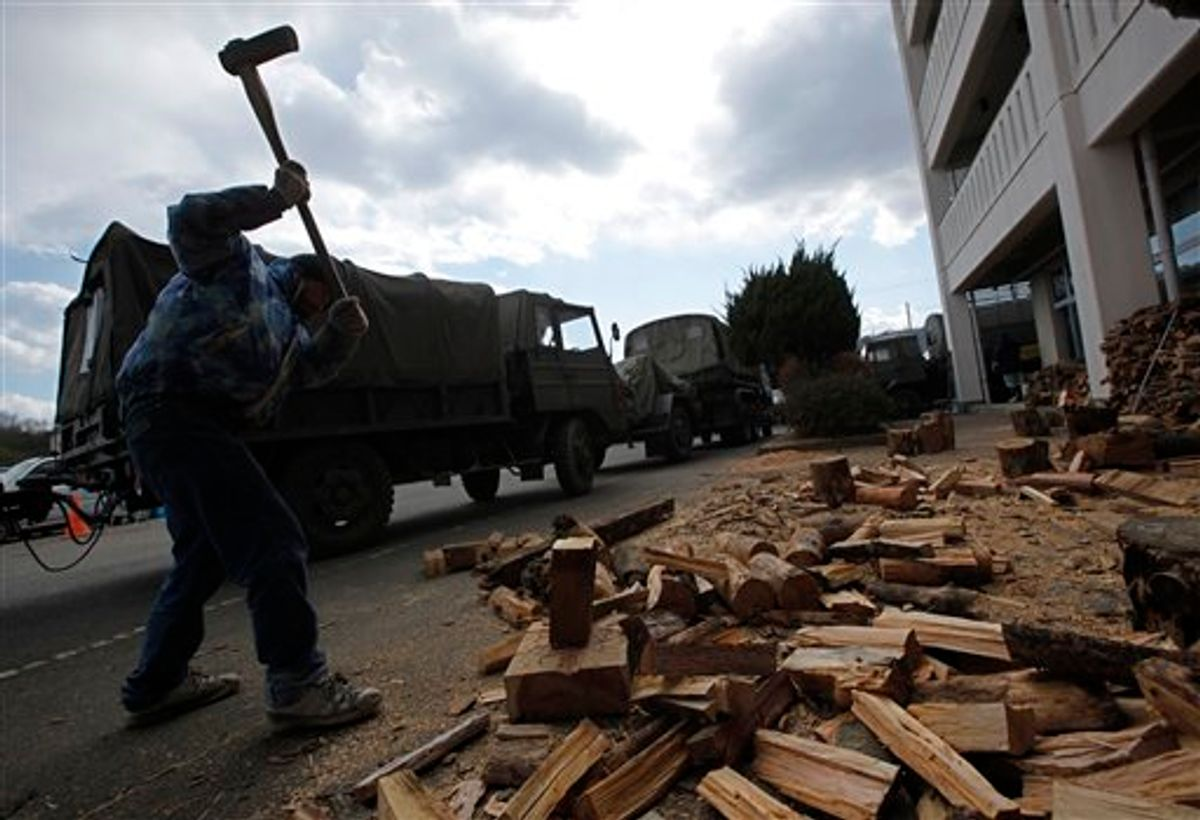 A survivor cuts woods for fire to warm at a shelter in the devastated town of Yamamoto, Miyagi Prefecture, northeastern Japan, Monday, March 28, 2011. The March 11 quake off Japan's northeast coast triggered a tsunami that barreled onshore and disabled the Fukushima nuclear complex. (AP Photo/Vincent Yu) (AP)