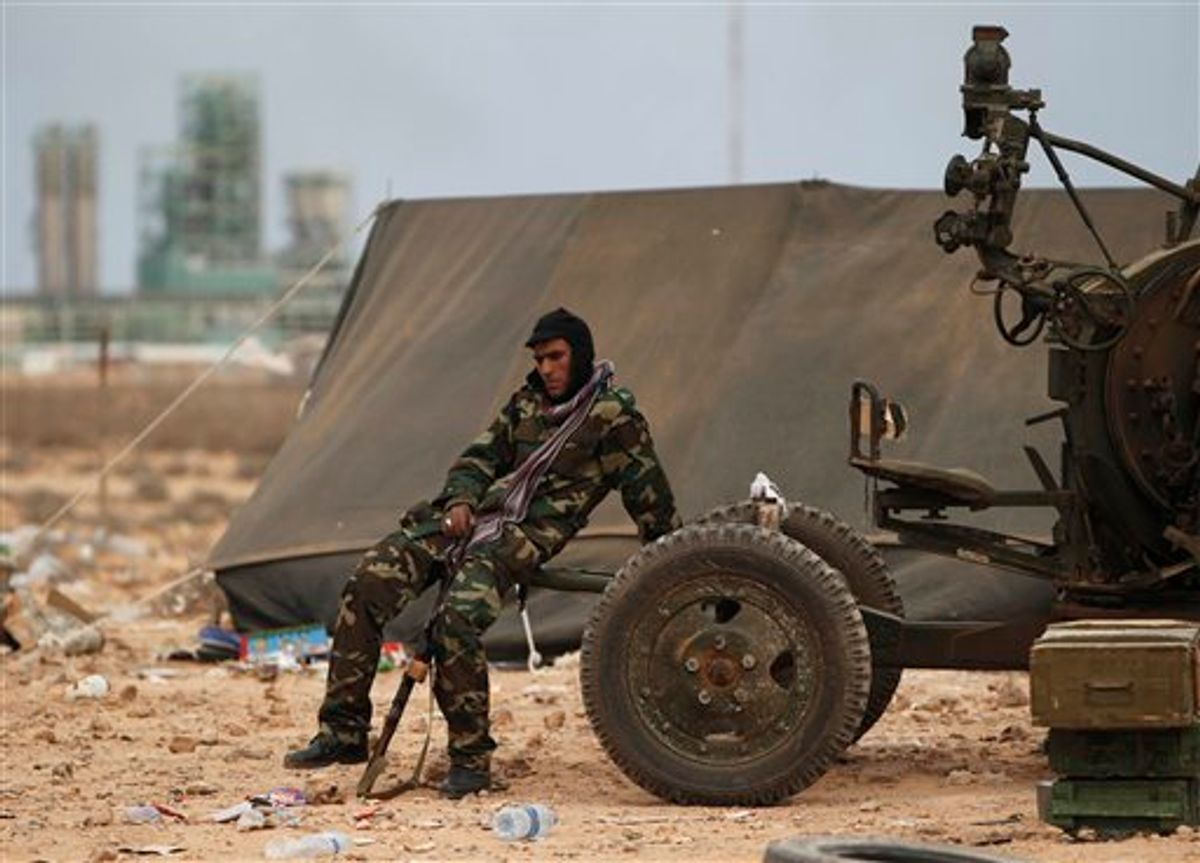 A Libyan volunteer sits near a weapon on the outskirts of the eastern town of Ras Lanouf, Libya, Thursday, March 10, 2011. Government forces drove hundreds of rebels from a strategic oil port with a withering rain of rockets and tank shells on Thursday, significantly expanding Moammar Gadhafi's control of Libya as Western nations struggled to find a way to stop him. (AP Photo/Tara Todras-Whitehill) (AP)