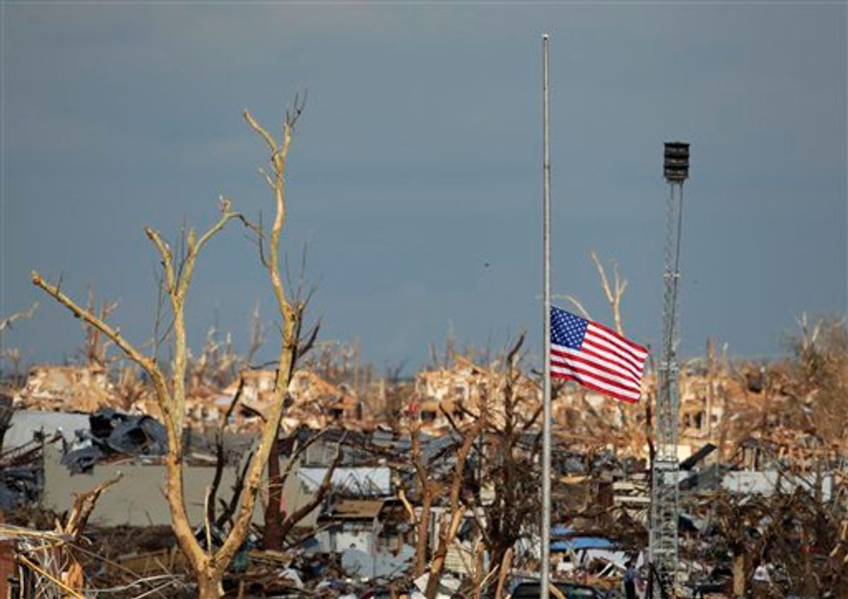 A flag files at half staff over devastated Joplin High School next to a portable tornado siren in Joplin, Mo. Thursday, May 26, 2011.  An EF-5 tornado tore through much of the city Sunday, damaging a hospital and hundreds of homes and businesses and killing at least 125 people. (AP Photo/Charlie Riedel) (AP)