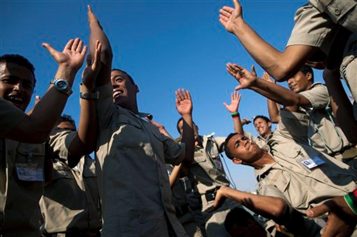 New cadets for the Libyan rebel army dance and chant anti Moammar Gadhafi  slogans before the ceremony graduation in Benghazi, Libya, Sunday, May 29, 2011.   (AP Photo/Rodrigo Abd) (AP)