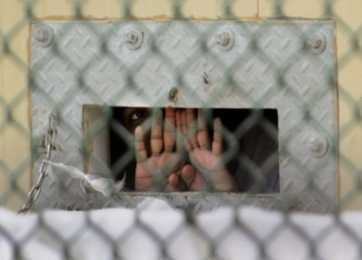 """A detainee shields his face as he peers out through the so-called """"bean hole"""" which is used to pass food and other items into detainee cells, at Camp Delta detention center, Guantanamo Bay U.S. Naval Base, Cuba, Monday, Dec. 4, 2006."""