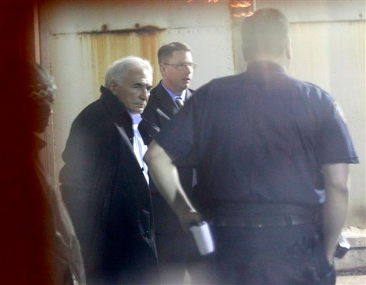 International Monetary Fund leader Dominique Strauss-Kahn, left, is seen through a window as he is checked into Municipal Court, Monday, May 16, 2011 in New York. Strauss-Kahn is accused of sexually assaulting a maid in his hotel room in New York City. (AP Photo/Julio Cortez) (AP)
