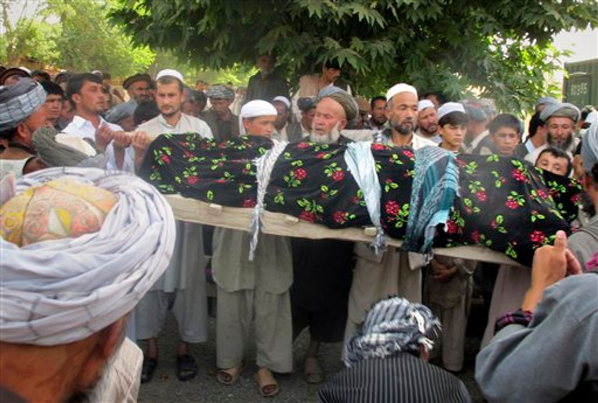 """Afghani people hold the lifeless body of one of the four Afghans, killed during a NATO raid in Taloqan, Takhar province, north of Kabul, Afghanistan on Wednesday, May 18, 2011.  More than 1,000 protesters poured into a northern Afghan city Wednesday, shouting """"Death to America!"""" and calling for justice as they clashed with security forces following an overnight NATO raid they claim killed four civilians. (AP Photo/Fulad Hamdard) (AP)"""