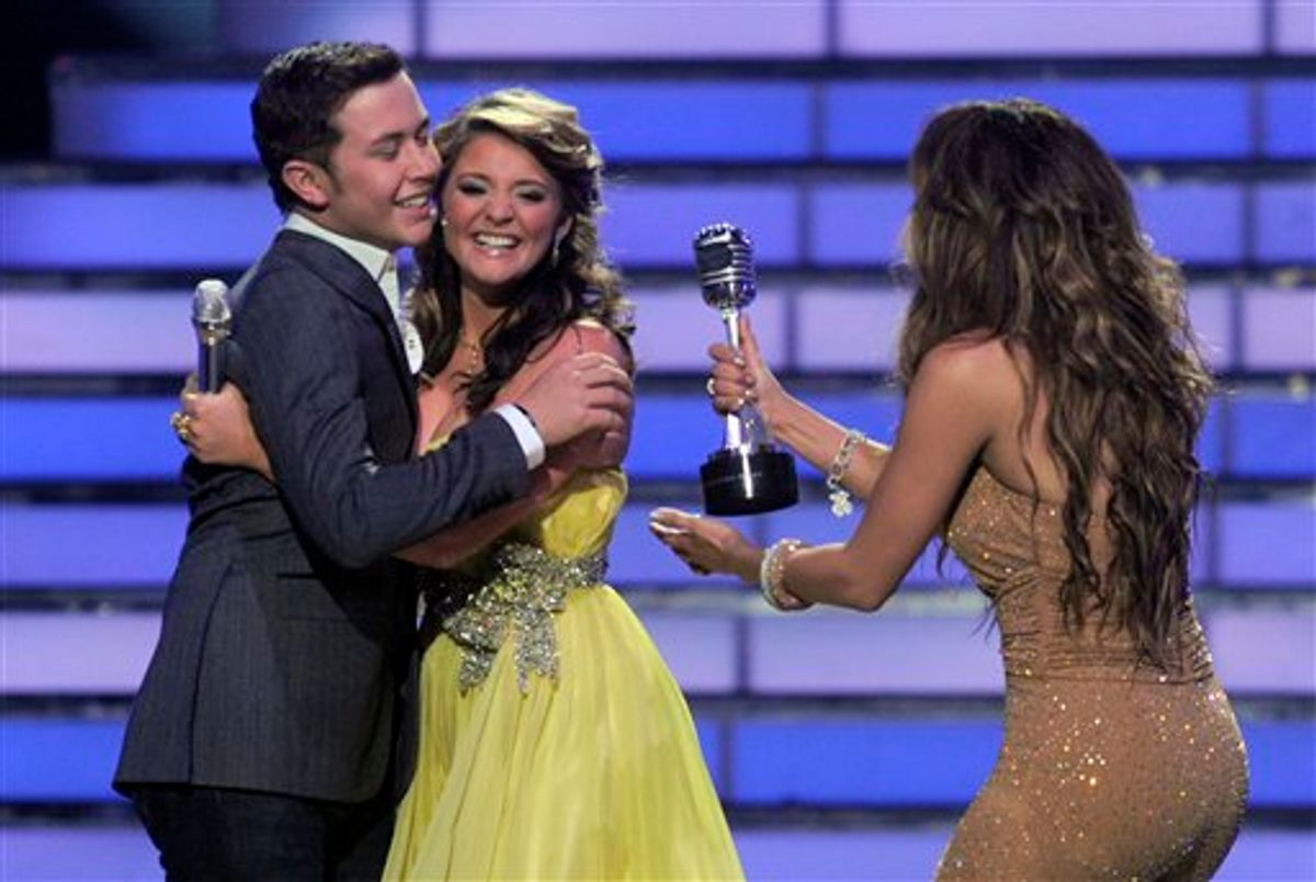 """Winner Scotty McCreery, left, hugs finalist Lauren Alaina as Jennifer Lopez hand him his trophy at the """"American Idol"""" finale on Wednesday, May 25, 2011, in Los Angeles. (AP Photo/Chris Pizzello)  (AP)"""