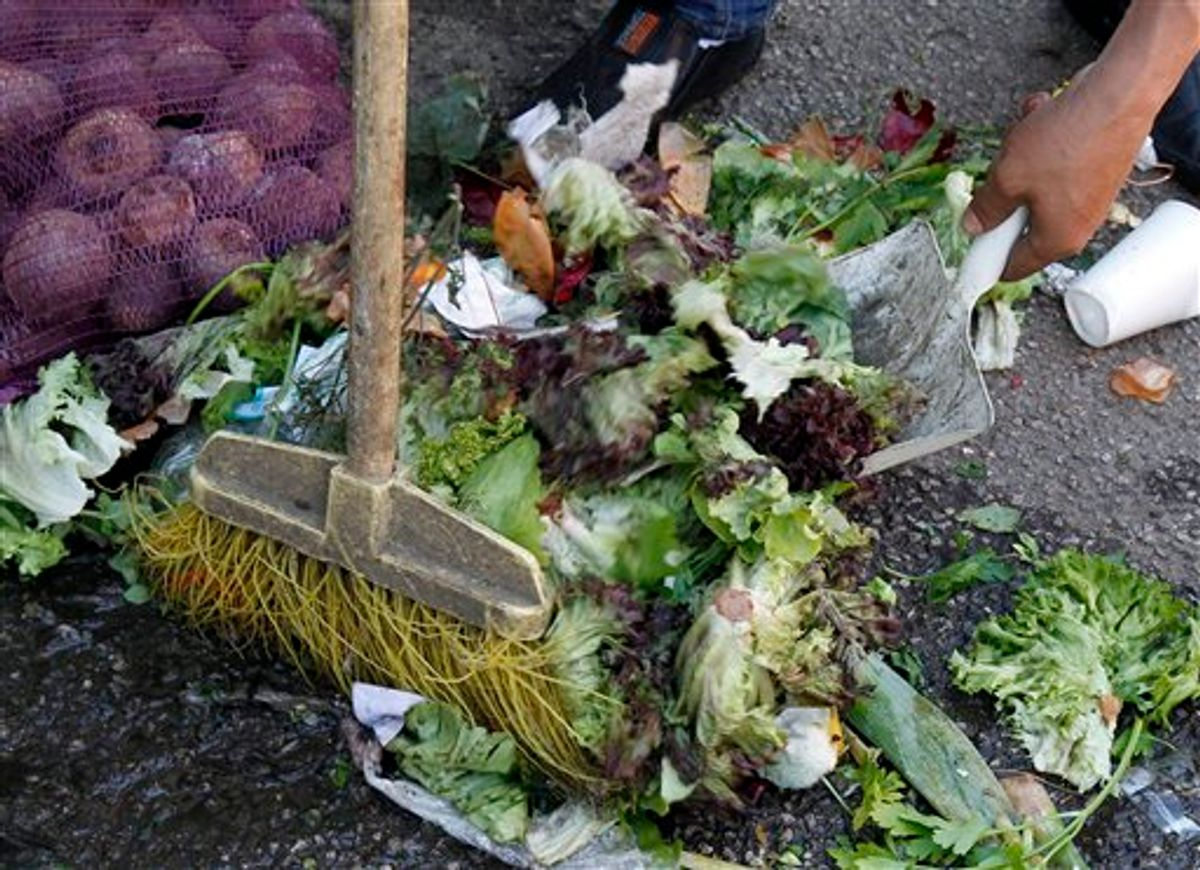 A man sweeps discarded salad vegetables from the floor at a food market in Vienna, Austria, on Monday May 30, 2011.  Vegetables from Spain are suspected of carrying the dangerous E.coli bacteria, which is suspected of killing some people in Germany and has caused many hundreds of people to become ill across Europe.  Austria has moved to ban the sale of cucumbers, tomatoes and eggplants that originated from Spain, although Spanish authorities said there is no proof that they are the source of the outbreak.(AP Photo/Ronald Zak) (AP)