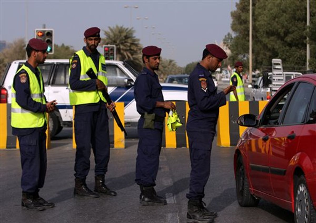 In this photo taken during a visit organized by Bahrain's Interior Ministry Bahrain police check a driver's identification at a checkpoint  in the capital of Manama, Bahrain  Monday, March 28, 2011. (AP Photo/Hasan Jamali) (AP)