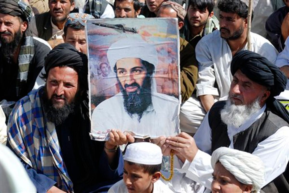 Supporters Pakistani religious party Jamiat Ulema-e-Islam hold al-Qaida leader Osama bin Laden's picture during a rally, in Kuchlak, 25 kilometers (16 miles) north of Quetta, Pakistan on Friday, May 6, 2011. One of three wives living with Osama bin Laden has told Pakistani interrogators she had been staying in the al-Qaida chief's hideout for six years without leaving its upper floors, a Pakistani intelligence official said Friday.(AP Photo/Arshad Butt) (AP)