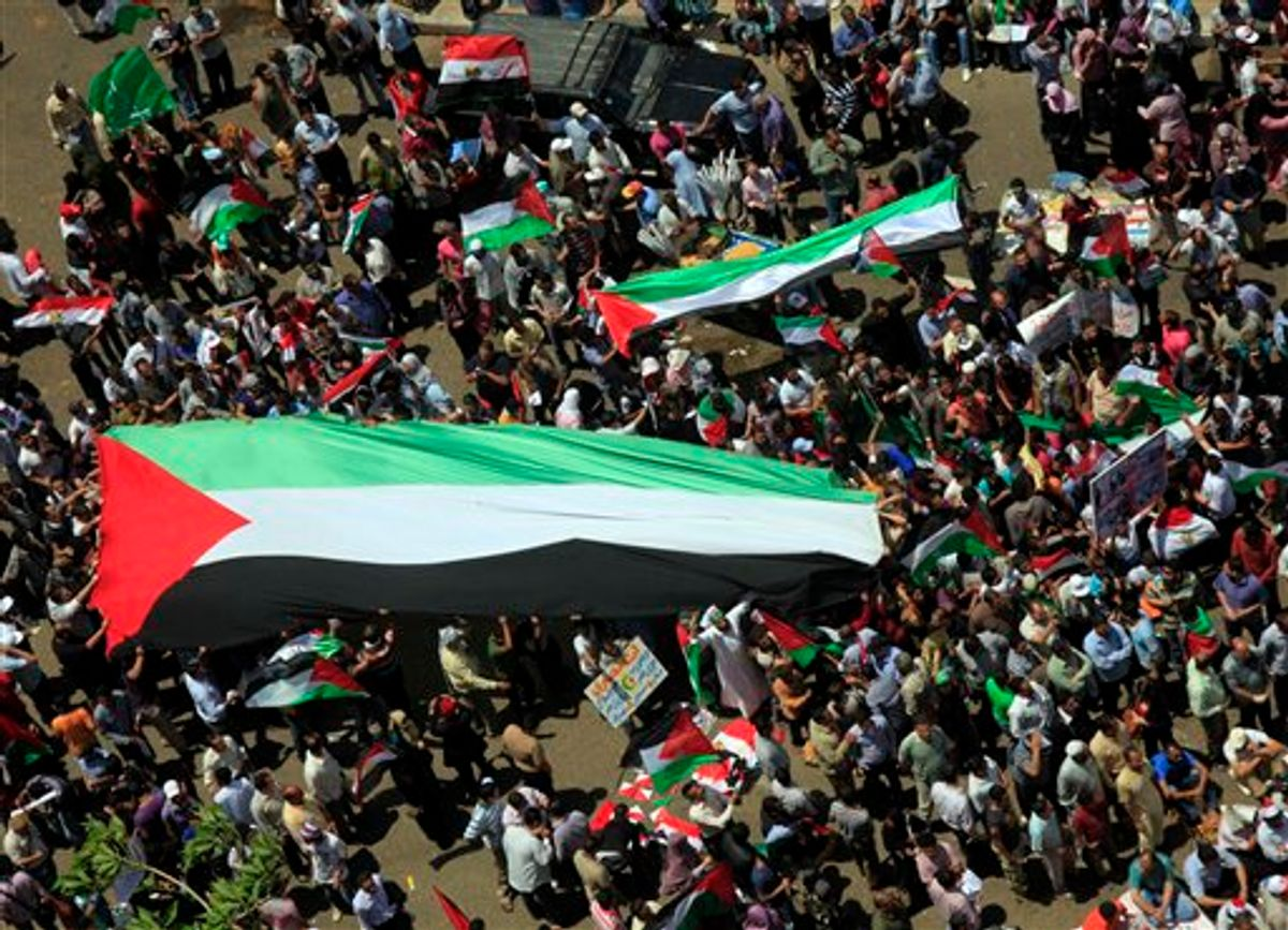 Egyptians carry a giant Palestinian flag during a protest against Israel's closure of Gaza as they march at Tahrir Square, the focal point of Egyptian uprising, in Cairo, Egypt Friday, May 13, 2011. (AP Photo/Amr Nabil) (AP)