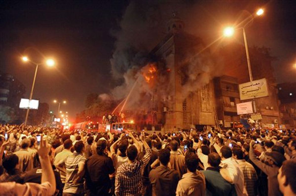 Firemen fight a fire at a church surrounded by angry Muslims in the Imbaba neighborhood in Cairo late Saturday, May 7, 2011. Christians and Muslims fought in the streets of western Cairo in violence triggered by word of a mixed romance, Egypt's official news agency reported. (AP Photo) (AP)