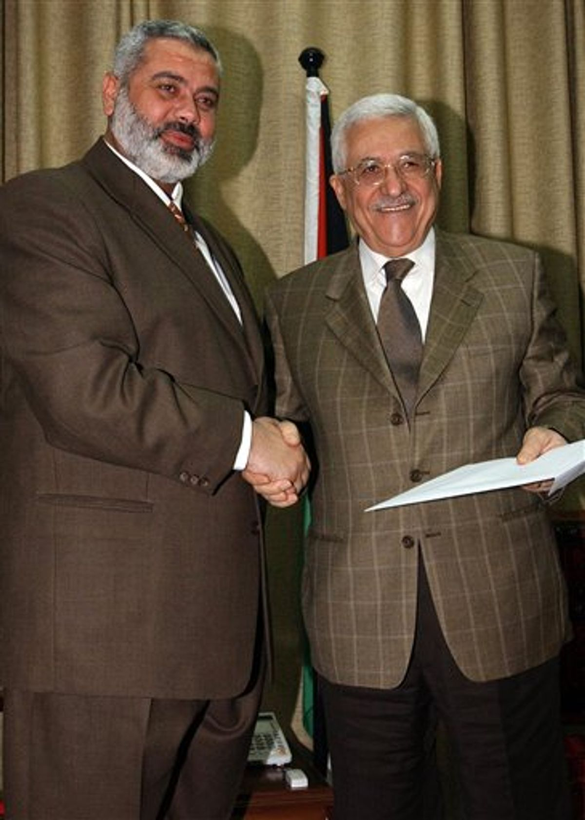 FILE - In this Sunday, March 19, 2006 file photo made available by the Palestinian Authority, the Palestinian Authority President Mahmoud Abbas, right, holds a file with the proposal for a new Palestinian Cabinet as he shakes hands with Palestinian Prime Minister Ismail Haniyeh, from the Islamic group Hamas, in Gaza City. Hamas officials said Tuesday, May 3, 2011, that the Islamic militant group would honor an unofficial truce with Israel after forming a new government with Palestinian rivals from the West Bank. (AP Photo/Abdel Alahim Abu Askar/Palestinian Authority, File)  (AP)