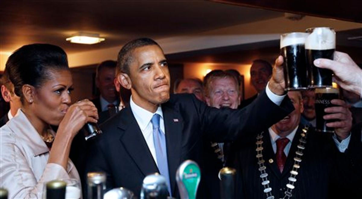 U.S. President Barack Obama and first lady Michelle Obama drink Guinness beer as they meet with local residents at Ollie Hayes pub in Moneygall, Ireland, the ancestral homeland of his great-great-great grandfather, Monday, May 23, 2011. (AP Photo/Charles Dharapak) (AP)
