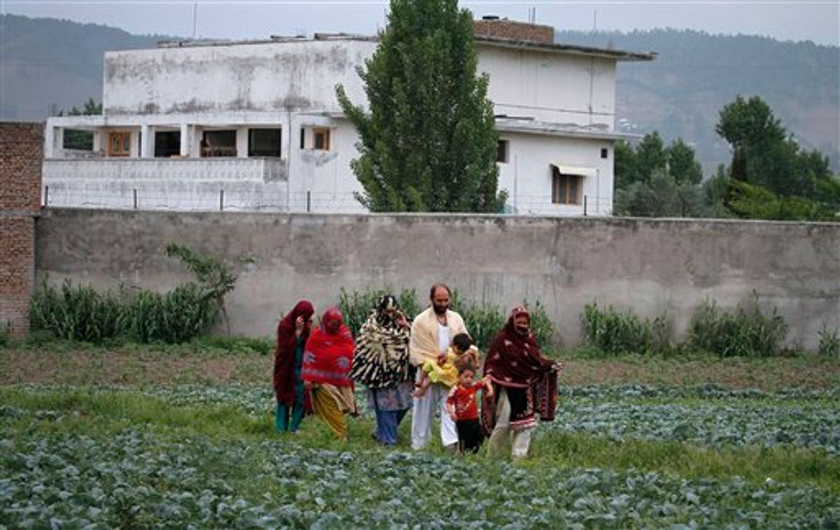 Pakistani family members leave the area after viewing the walled compound of a house, seen in background, where al-Qaida leader Osama bin Laden was caught and killed in Abbottabad, Pakistan, on Thursday,  May 5, 2011.  The residents of Abbottabad, Pakistan, seem to be confused and suspicious about the killing of Osama bin Laden by a U.S. military force, which took place in their midst before dawn on Monday. (AP Photo/Anjum Naveed) (AP)