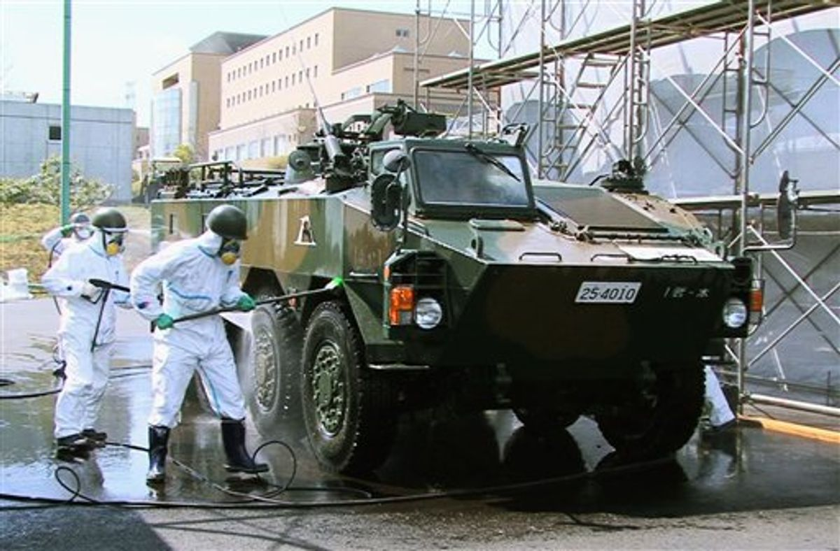 In this April 12, 2011 photo released by the Japan Defense Agency via Kyodo News, Japanese soldiers wash an armored vehicle to remove potential radiation contamination at J-Village, a soccer training complex now serving as an operation base for those battling Japan's worst nuclear disaster, northeastern Japan. The sports complex is about about 20 kilometers (12 miles) from the crippled Fukushima Dai-ichi nuclear plant. (AP Photo/Japan Defense Agency via Kyodo News) JAPAN OUT, MANDATORY CREDIT, NO LICENSING IN CHINA, HONG KONG, JAPAN, SOUTH KOREA AND FRANCE (AP)