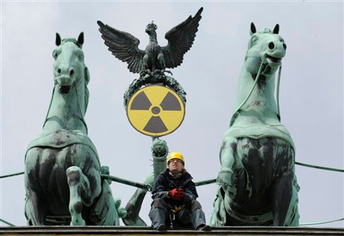 An environmental activist sits on top of the Brandenburg Gate after Greenpeace activists fixed a radioactive sign to the Quadriga in Berlin, Sunday May 29, 2011 to protest against the nuclear power policy of German Government. (AP Photo/dapd/Michael Gottschalk) (AP)