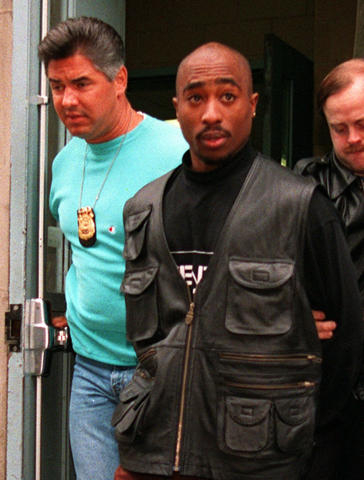 Rap star Tupac Shakur is led from the Manhattan North police precinct after being arrested in an alleged sexual attack on Nov. 19, 1993.  (AP Photo/Justin Sutcliffe) (Associated Press)
