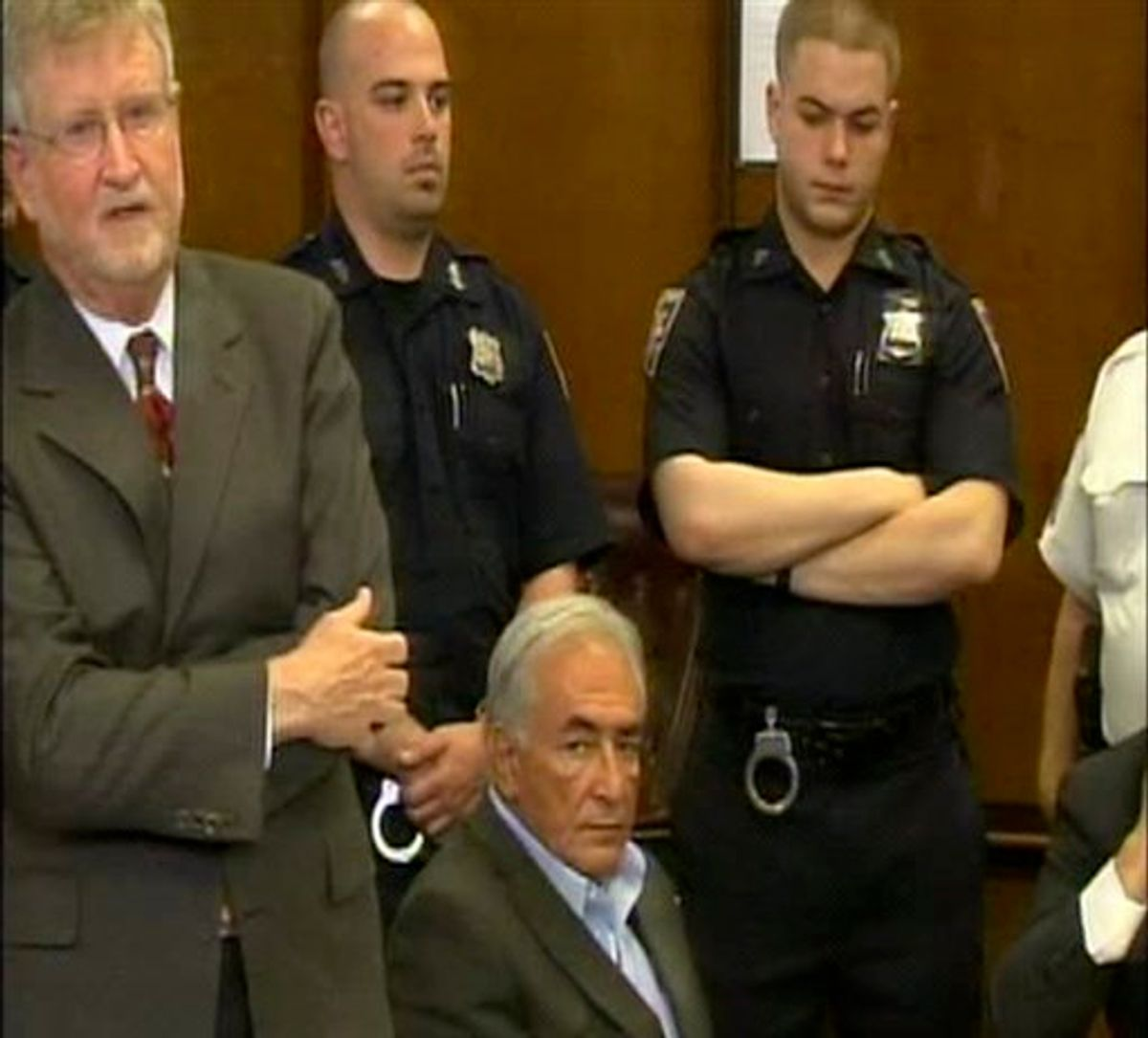 This frame grab taken from pool video shows former IMF leader Dominique Strauss-Kahn, center, seated, as he appears at a court hearing in the Manhattan borough of New York, Thursday May 19, 201, surrounded by his lawyer William Taylor, left, and unidentified police officers. Strauss-Kahn made a new bid to get released from jail while he awaits trial on charges that he sexually abused a hotel maid. A prosecutor began the hearing by announcing that a grand jury had found enough evidence for an indictment, a procedural step that elevates the seriousness of the charge. (AP Photo/NBC, Pool) (AP)