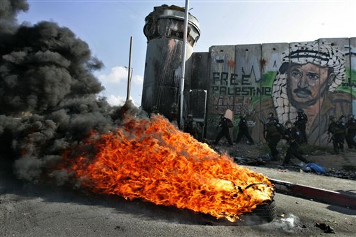 """Israeli soldiers run past burning tires under a mural of the late Palestinian leader Yasser Arafat during clashes with Palestinian stone throwers following a protest to mark the upcoming 63rd anniversary of """"Nakba"""", Arabic for """"Catastrophe"""", the term used to mark the events leading to Israel's founding in 1948, in the Qalandia checkpoint between Ramallah and Jerusalem, Saturday, May 14, 2011.(AP Photo/Majdi Mohammed) (AP)"""