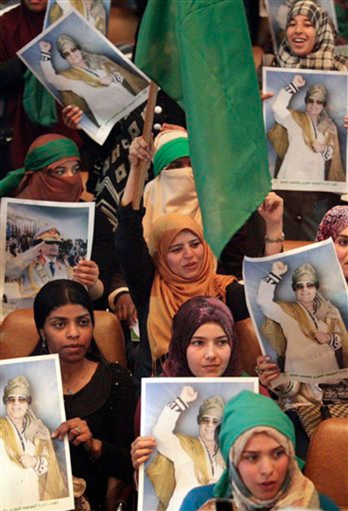In this image taken during a trip organized by Libyan authorities, students hold portraits of Libyan leader Moammar Gadhafi during a meeting at  the Al Fateh University in Tripoli, Libya, celebrating Student Day,  Thursday, April 7, 2011. (AP Photo/Pier Paolo Cito) (AP)