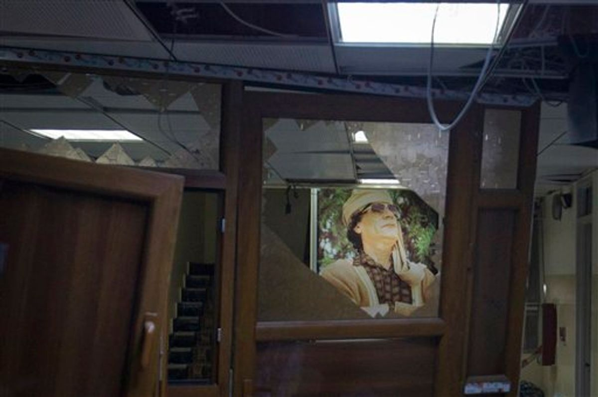 In this photo taken on a government organized tour, a poster of Libyan leader Moammar Gadhafi is seen in a damaged official building following an airstrike in Tripoli, Libya, early Tuesday, May 17, 2011. (AP Photo/Darko Bandic) (AP)