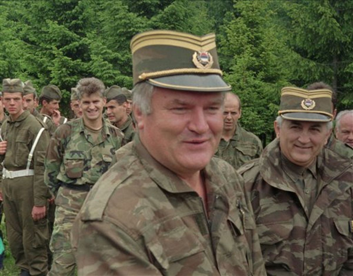 FILE In this June 28, 1996 file photo Bosnian Serb military commander General Ratko Mladic, center, smiles as he visits troops to mark both the fourth anniversary of the founding of his Bosnian Serb army and St. Vitus' Day, the anniversary of the Serb defeat by the Turks at Kosovo in 1389, near the village of Han Pijesak, some 40 miles east of Sarajevo. Belgrade media reports Thursday May 26, 2011 that a man suspected to be Europe's most wanted war crimes fugitive Ratko Mladic has been arrested in Serbia. Serbia state TV said a man who identified himself as Milorad Komadic when he was arrested Thursday is the wartime Bosnian Serb army commander. It gave no other details. (AP Photo) (AP)