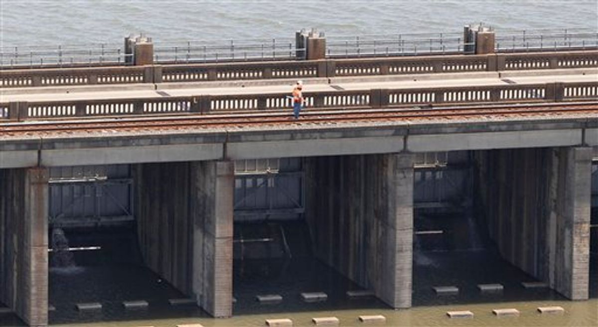 Workers stand atop the Morganza Spillway in Morganza, La., Thursday, May 12, 2011, as water seeps through, bottom, during an aerial tour of areas that may be affected by flooding if the spillway is opened. (AP Photo/Patrick Semansky) (AP)