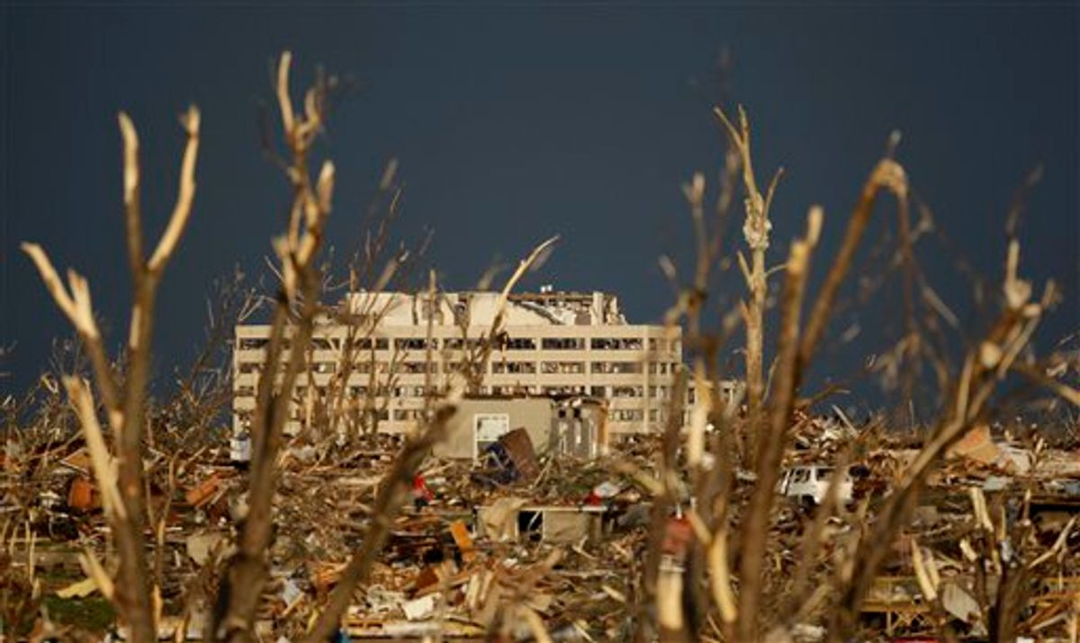 The damaged St. John's Regional Medical Center is seen in the distance through tornado debris in Joplin, Mo., Monday, May 23, 2011. A large tornado moved through much of the city Sunday, damaging the hospital and hundreds of homes and businesses and killing at least 89 people. (AP Photo/Charlie Riedel) (AP)