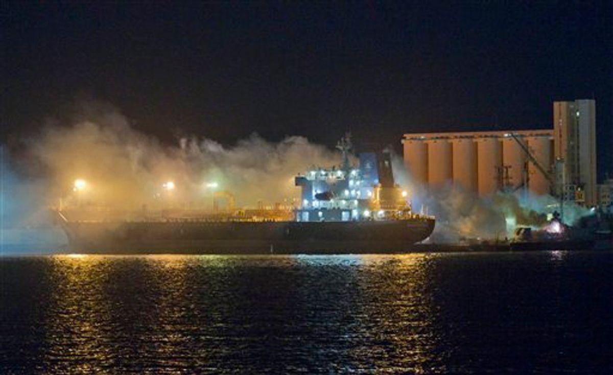 Smoke rises from a ship that was hit in an airstrike, at Tripoli sea port, Libya, early Friday, May 20, 2011. (AP Photo/Darko Bandic) (AP)