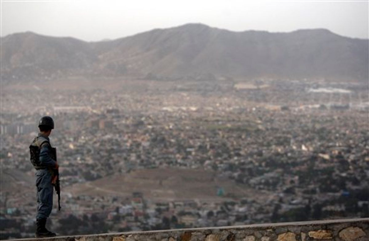 An Afghan policemen stands guard as an aerial view of Kabul city is seen from atop a hill in Kabul, Afghanistan, Friday, May 27, 2011. (AP Photo/Mustafa Quraishi) (AP)