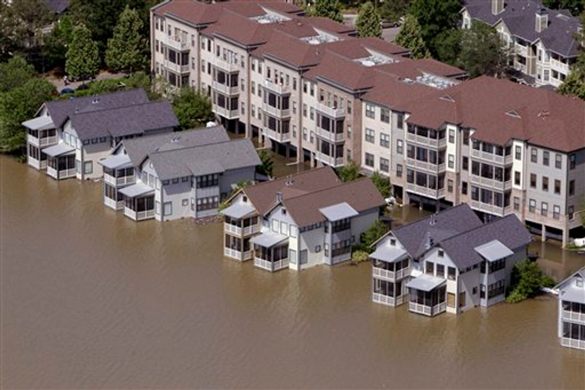 Homes on Mud Island sit in floodwater Tuesday, May 10, 2011, in Memphis, Tenn. The Mississippi River crested in Memphis at nearly 48 feet on Tuesday, falling short of its all-time record but still soaking low-lying areas with enough water to require a massive cleanup. (AP Photo/Jeff Roberson) (AP)