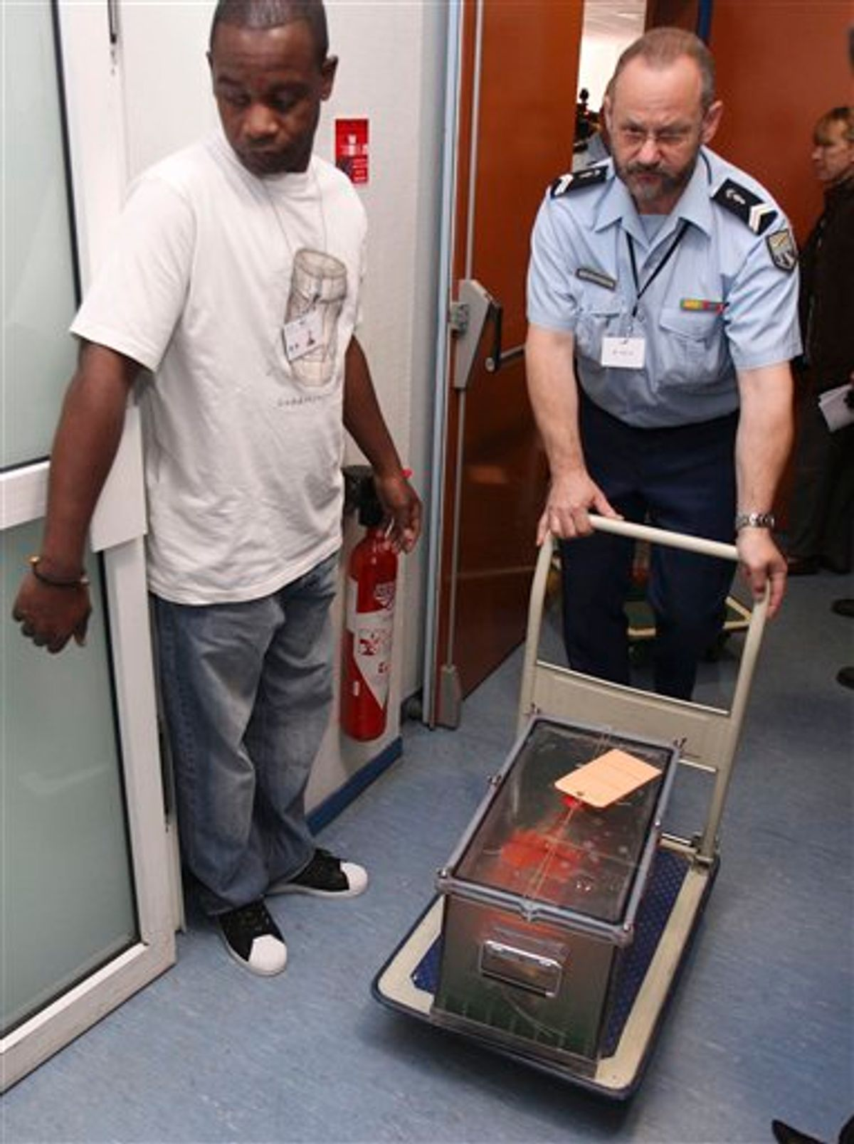 FILE- This Thursday, May 12, 2011 file photo shows a police officer pushing one of the two flight recorders of the Air France flight 447, who crashed in 2009, after they were displayed to reporters during a press conference at the French investigators' headquarters in Le Bourget, near Paris. Officials say flight recorders from an Air France plane that crashed nearly two years ago show that the captain only arrived in the cockpit after the plane had begun its fateful 3 1/2-minute descent. The initial findings of the French air accident investigation agency, the BEA, based on a reading of the so-called black boxes recovered from the ocean depths, found that the captain had been resting when the emergency began.All 228 aboard the Rio de Janeiro to Paris flight were killed on June 1, 2009. (AP Photo/Michel Euler, File)  (AP)