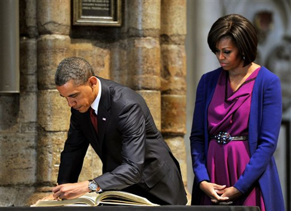 US President Barack Obama,  watched by his wife, first lady Michelle Obama, signs the distinguished visitors book during a tour of Westminster Abbey, in central London, Tuesday May 24, 2011. President Barack Obama and first lady Michelle Obama traded-in Irish charm for the pomp and pageantry of Buckingham Palace Tuesday as they opened a state visit to Britain at the invitation of Queen Elizabeth II. (AP Photo/John Stillwell/Pool) (AP)