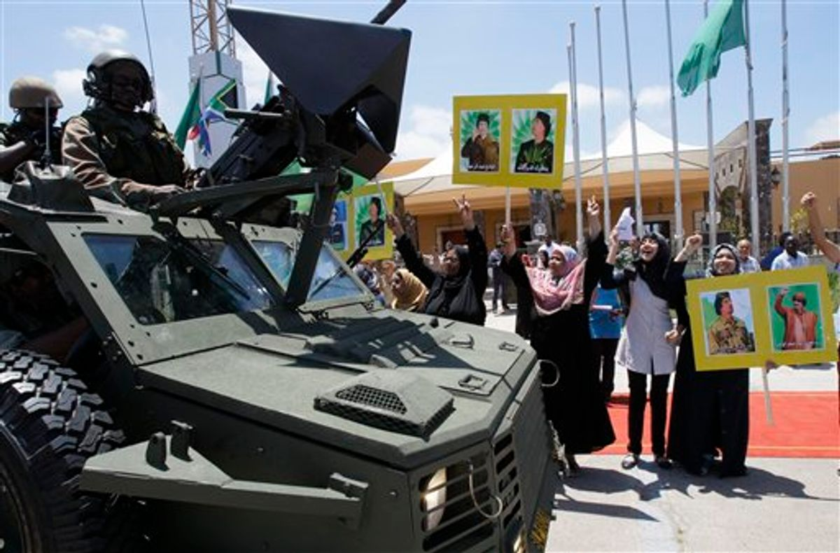 Local residents hold portraits of Libyan leader Moammar Gadhafi and chant as they greet South African security personnel guarding President Jacob Zuma's motorcade leaving the airport in Tripoli, Libya, on Monday, May 30, 2011. (AP Photo/Ivan Sekretarev) (AP)